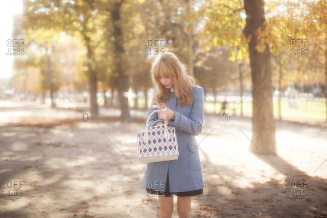 Woman standing in a city park in autumn wearing a mod overcoat and reaching into her purse