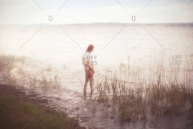 Woman standing in the water along a lake shore