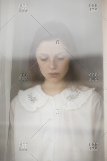 Portrait of a woman in a white blouse standing in a window