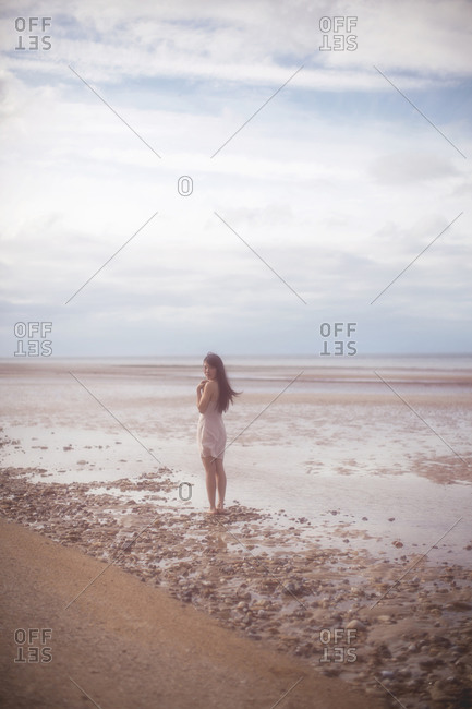 Woman standing in the water along a beach