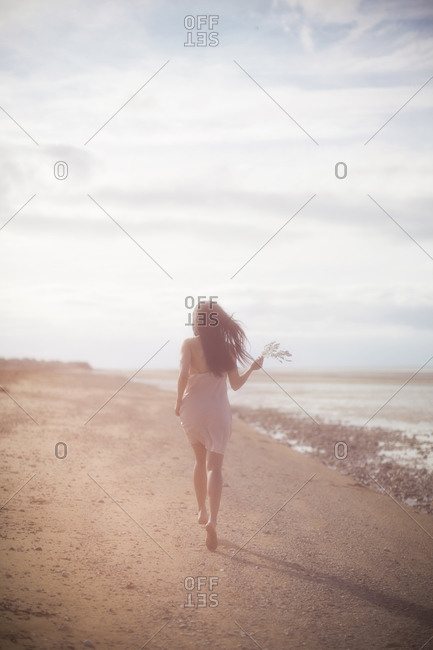 Woman running along the beach holding a wildflower