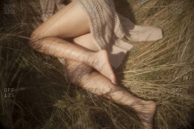Overhead view of a woman lying in tall grass with a sweater draped across her legs