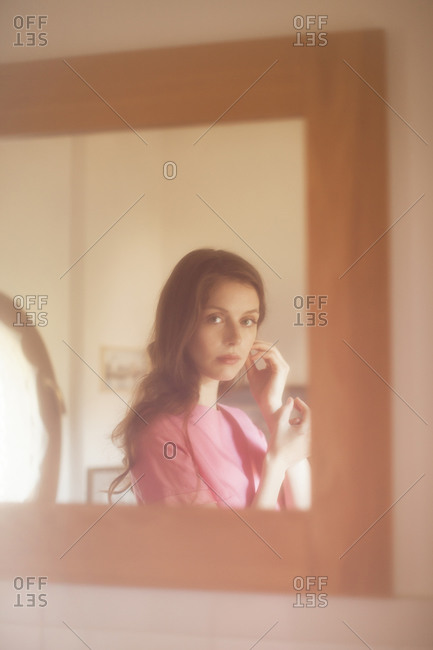 A reflection in a mirror of a woman putting in earrings