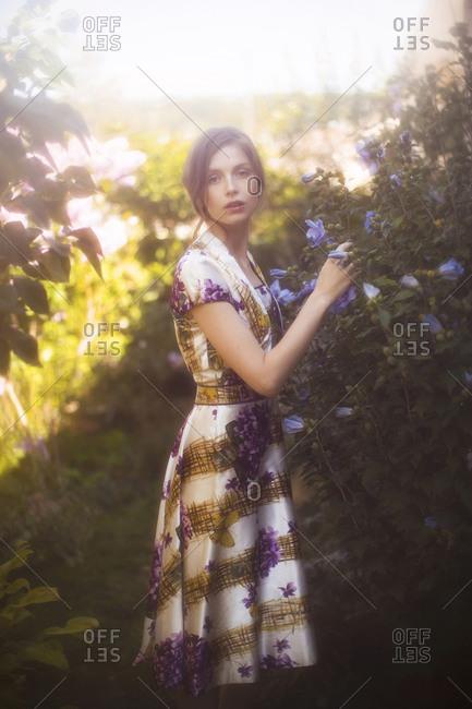 Portrait of a woman in a dress picking flowers in a garden