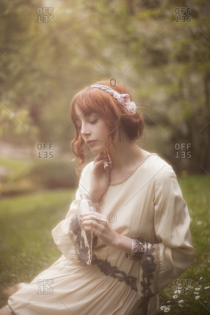 A woman sitting in a garden applying perfume to her neck