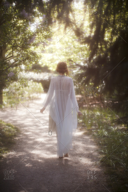 A woman dressed in a sheer white dress walking down a wooded garden path