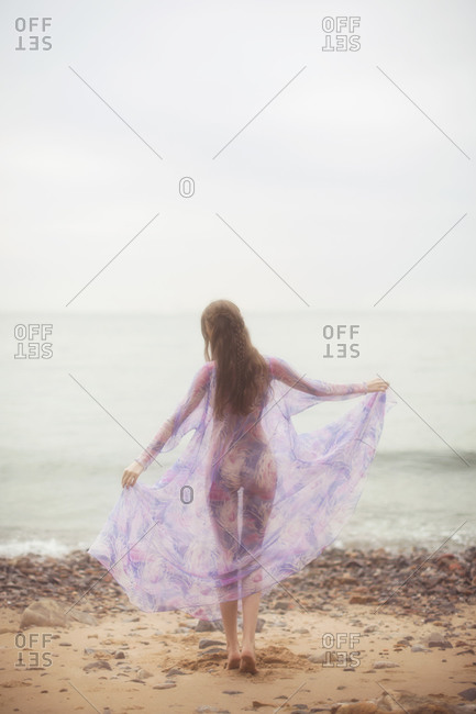 Woman standing along a rocky beach looking out to sea