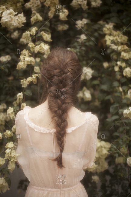 Woman with braided hair in a sheer dress looking at flowers in a garden