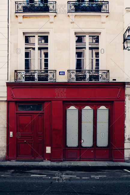 Residential building in Paris with a red door viewed from the street