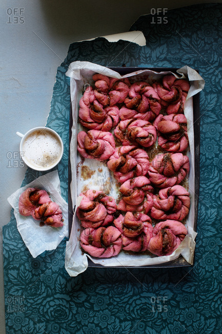 Swedish cinnamon buns with beetroot and a cup with coffee and milk