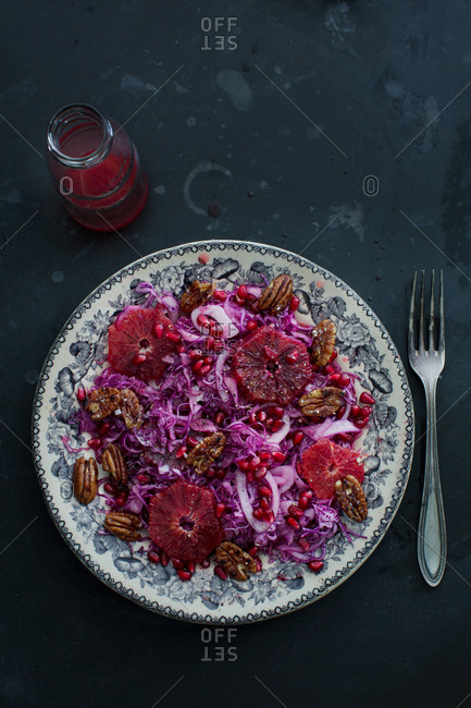 Salad made with red cabbage, blood oranges, pomegranate, pecans, and red onion with a blood orange and olive oil dressing