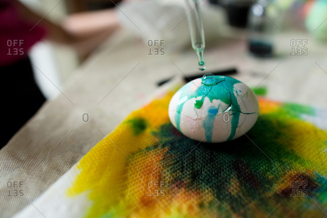 Close-up of an eye dropper being used to color a cracked Easter egg