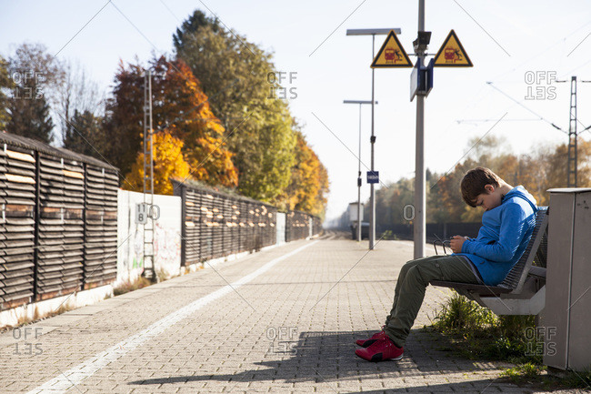 Side view of boy using mobile phone on railroad station