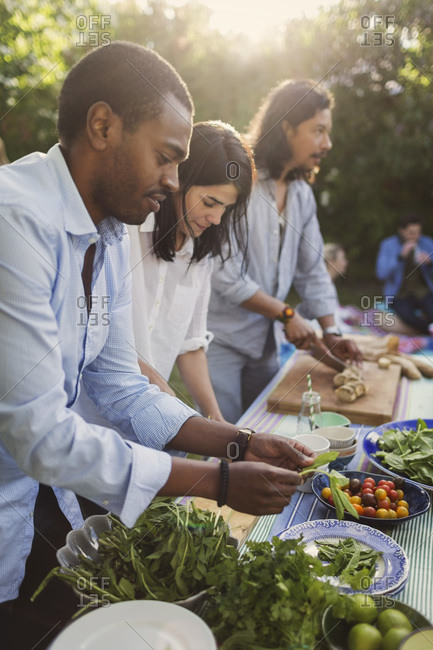 Multi-ethnic friends preparing food together at table in yard during summer party