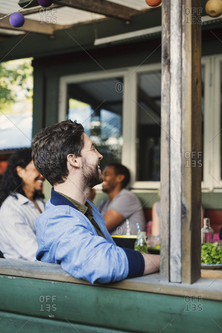 Side view of happy man sitting at porch while enjoying summer party with friends