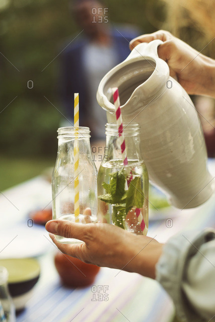 Woman serving mojito in bottle at summer party