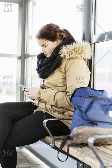 Young woman using mobile phone on bench at train station
