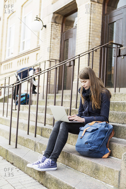 Young woman using laptop on steps of high school