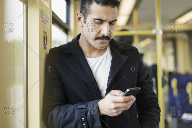 Young man using mobile phone in tram