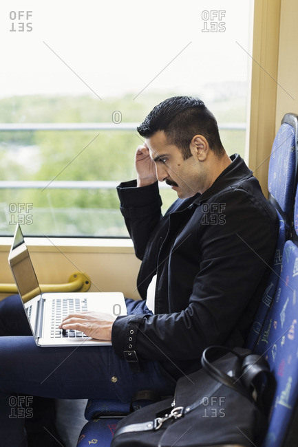 Side view of young man using laptop in tram