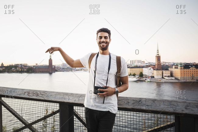Optical illusion of happy male tourist holding building in city against clear sky