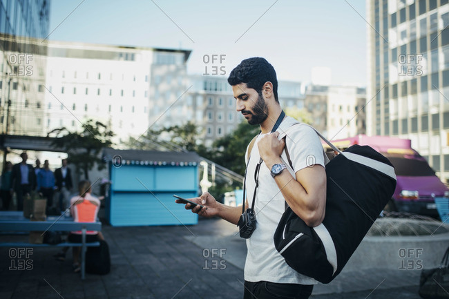 Side view of male tourist using smart phone in city