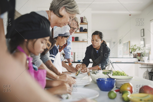 Woman guiding family in preparing food at kitchen