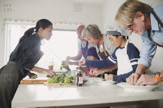 Woman guiding family in preparing Asian food at kitchen