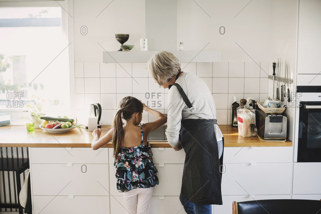 Rear view of girl standing with grandmother preparing food in kitchen