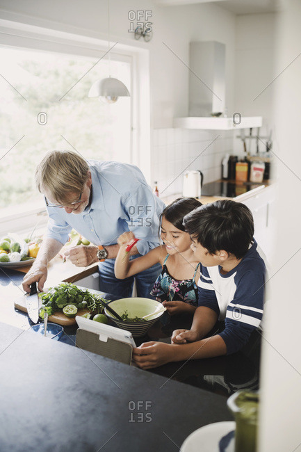 Happy grandfather and children preparing food at kitchen counter