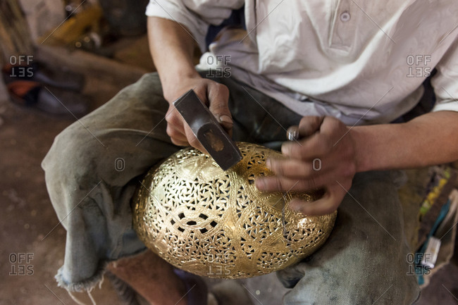Close up of a man carving a gold metal handcraft in his shop in Marrakesh