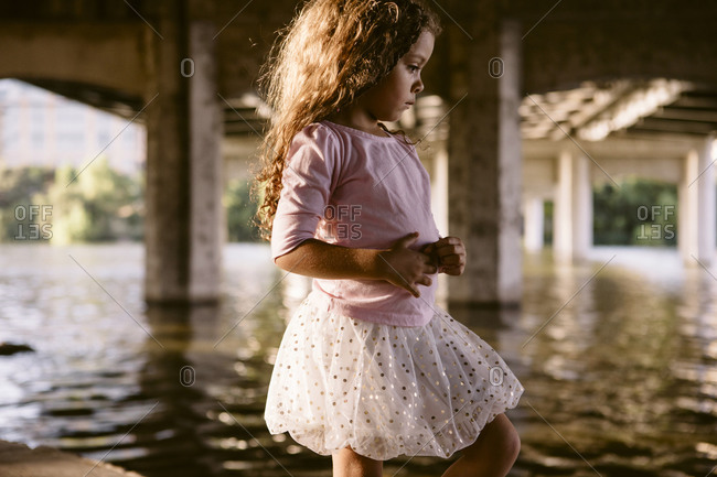Girl standing by river under bridge