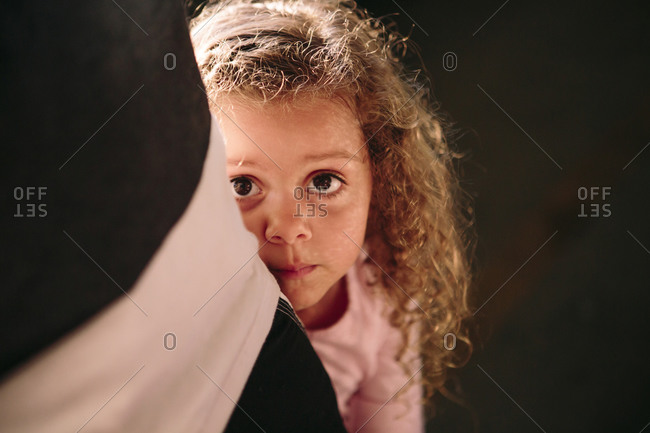 Girl hiding behind adult - from the Offset Collection