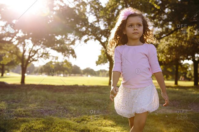 Girl walking in summer sunlight