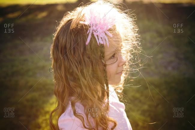 Sun dappled girl with flower in hair
