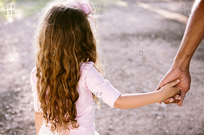 Girl holding on to man's hand