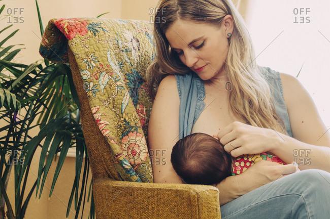 Mom breastfeeding infant in armchair