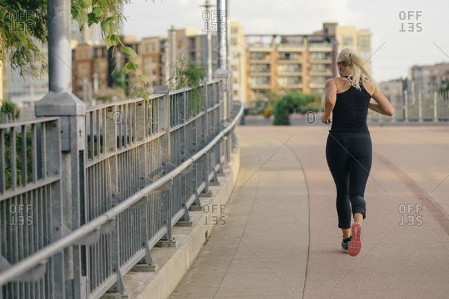 Woman jogging on a city sidewalk in Austin, Texas