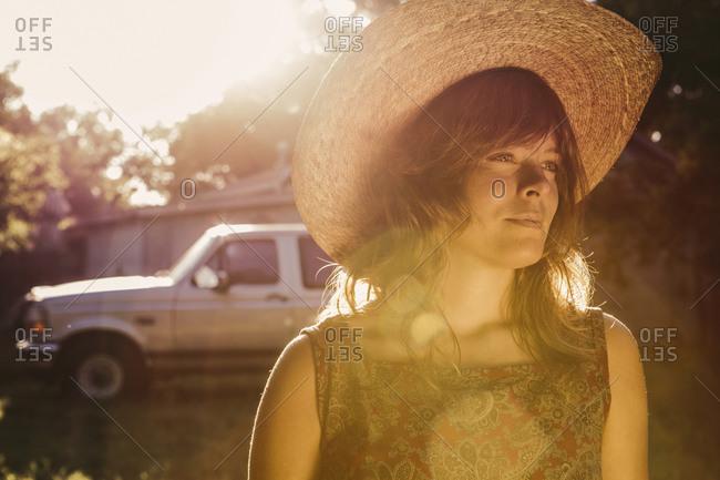 Woman wearing a cowboy hat standing near a truck