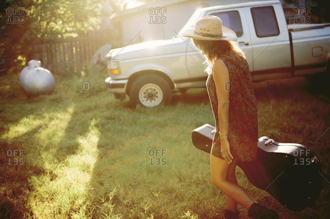 Woman walking toward a retro truck carrying a guitar case