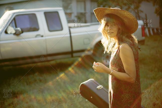 Woman carrying a guitar case toward a truck
