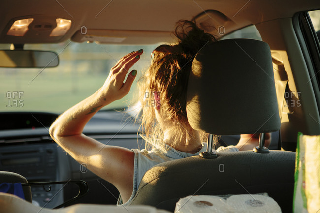 Woman in the passenger seat of a car fixing her hair