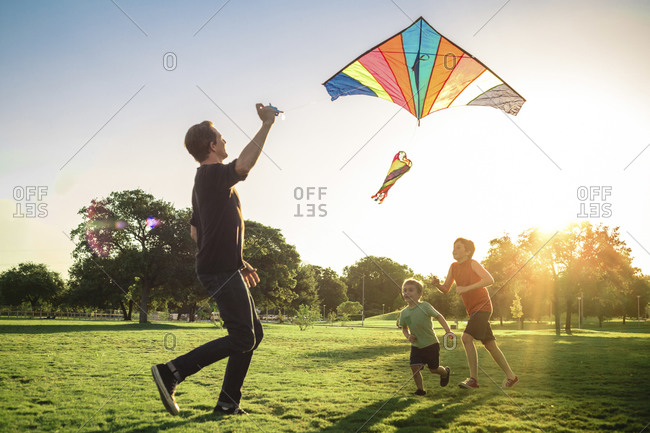 Father and two sons flying a kite