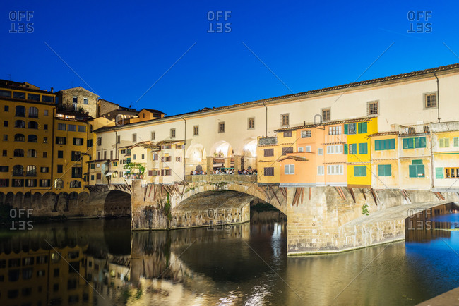 A view at dusk of the Ponte Vecchio along the Arno River in Florence, Italy