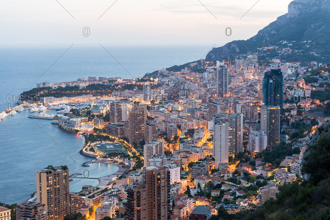 A view of the city of Monaco from a hillside at dusk