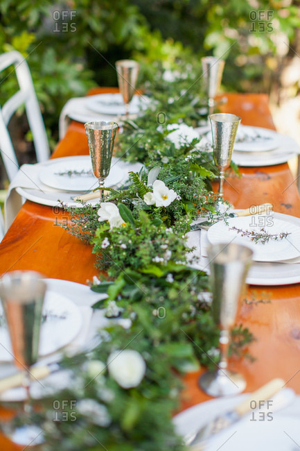 Dining table set with garland of greenery for outdoor wedding reception