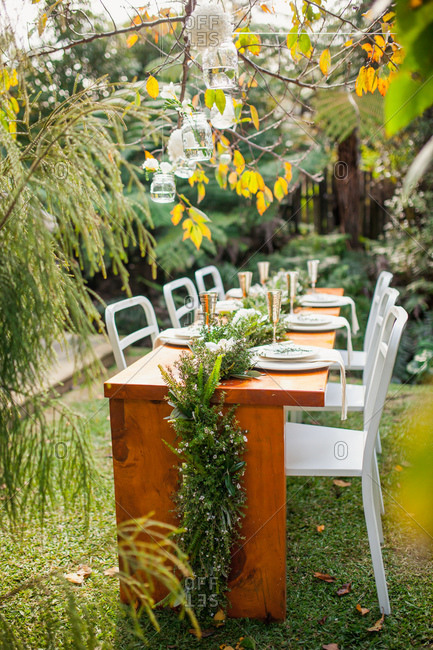Dining table set in garden for outdoor wedding reception