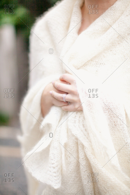 Woman wrapped in white knitted shawl