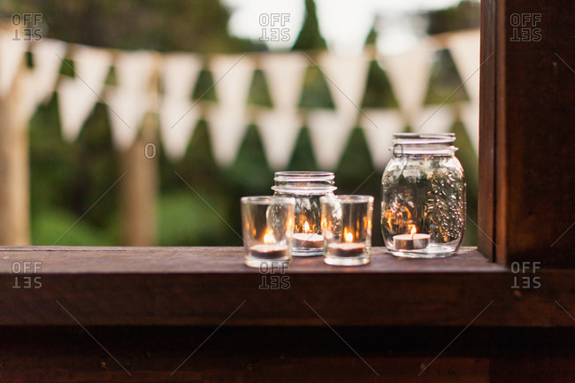 Tea light candles in glass jars on windowsill at outdoor wedding reception