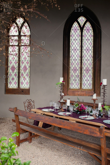 Rustic wooden dining table set next to gothic stained glass windows